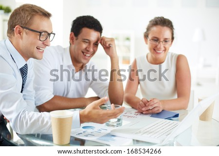 Portrait of successful businessman pointing at laptop screen while explaining something to his colleagues at meeting - stock photo