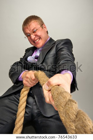 Portrait of successful businessman pulling a rope - stock photo