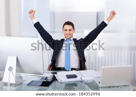 Portrait of successful businessman with arms raised sitting at desk in office - stock photo