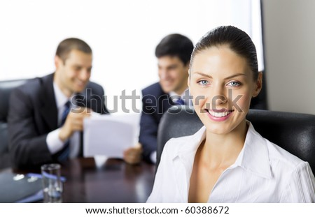 Portrait of successful businesswoman and colleagues on background, at office - stock photo