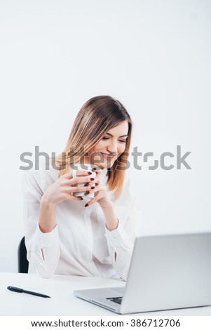 Portrait of successful businesswoman working with laptop in office. Young business lady smiling and sitting with laptop..Young businesswoman on a coffee break. businesswomen enjoying coffee  - stock photo