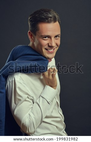 Portrait of successful cheerful handsome businessman in elegant formal wear posing with blue jacket over his shoulder. - stock photo