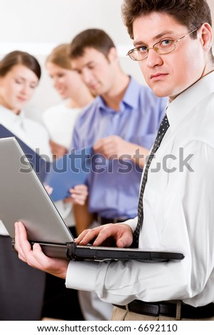 Portrait of successful chief holding the laptop on the background of his business team