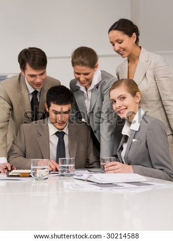 Portrait of successful employees looking at papers while confident woman smiling at camera during meeting - stock photo