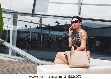 Portrait of successful female calling with smart phone while sitting against modern office building in summer day, confident young woman using cell telephone while enjoying rest after hard work day  - stock photo