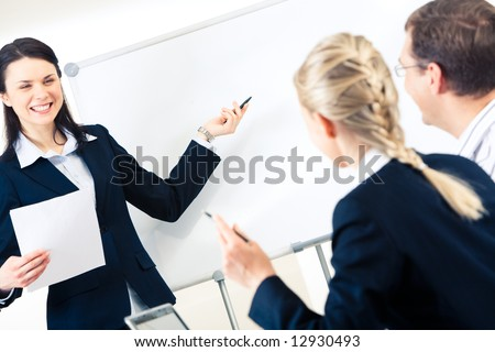 Portrait of successful girl explaining something on whiteboard to her colleagues - stock photo