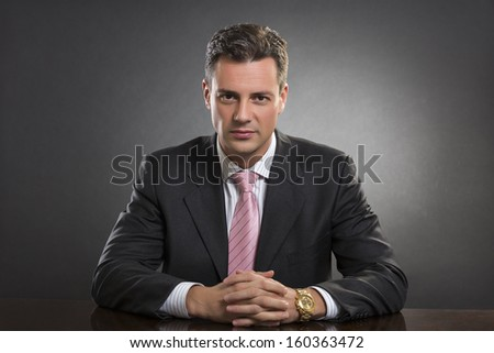 Portrait of successful handsome well-dressed young businessman looking confidently at camera in his office over dark background. Smart people. - stock photo