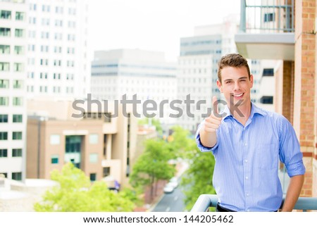 Portrait of successful, happy, handsome guy giving thumbs up on his balcony, isolated on a city background with trees - stock photo