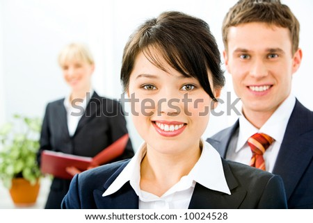 Portrait of successful leader with business team in the background - stock photo