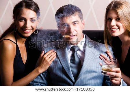 Portrait of successful man smoking a cigar holding whisky with pretty women near by