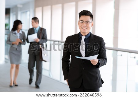 Portrait of successful manager on the background of his colleagues discussing a document - stock photo