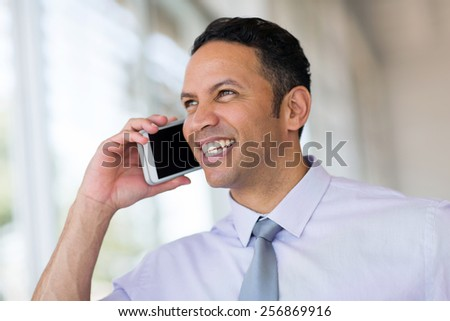 portrait of successful middle aged businessman talking on mobile phone - stock photo