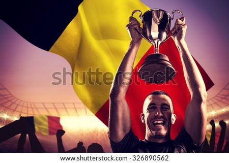 Portrait of successful rugby player holding trophy against large football stadium under purple sky - stock photo