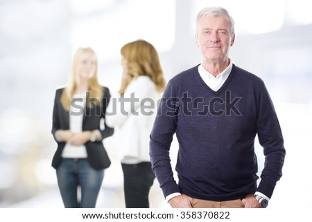 Portrait of successful senior professional man standing at office while group of business people consulting at background.