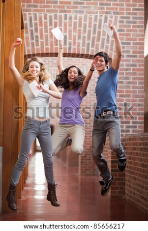 Portrait of successful students jumping in a corridor - stock photo
