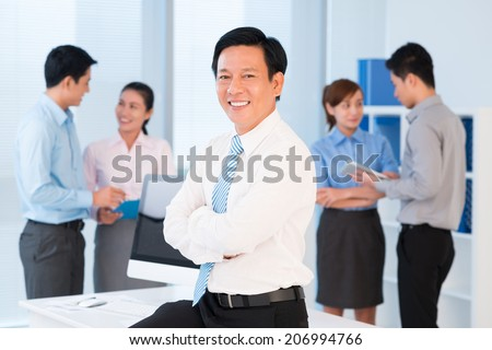 Portrait of successful Vietnamese businessman in working environment - stock photo