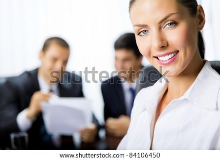 Portrait of successful young happy smiling successful business woman and colleagues on background, at office
