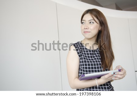 Portrait of successful young smiling businesswoman working with tablet in office