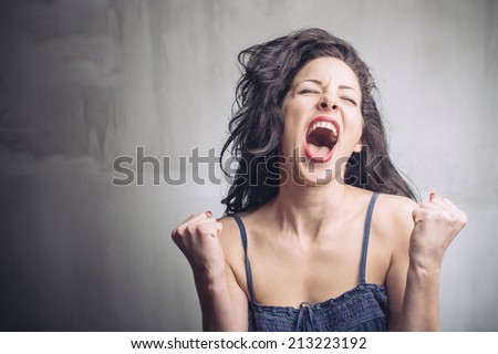 Portrait of successful young woman with fists clenched  - stock photo