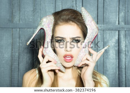 Portrait of sullen glamour fashion young girl with long beautiful hair holding shoe in hand near face as mobile phone on wooden background, horizontal picture - stock photo