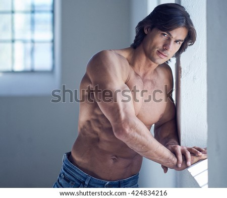 Portrait of suntanned muscular guy in denim jeans.