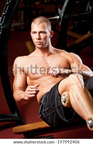 Portrait of super fit muscular young man working out in gym.