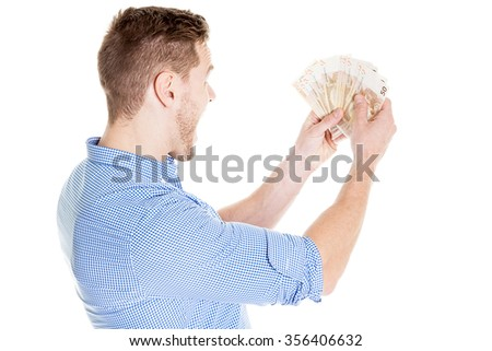 portrait of super happy excited successful young man holding money dollar bills in hand, isolated on white background. Positive emotion facial expression feeling. Financial reward savings - stock photo