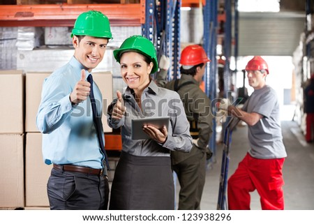 Portrait of supervisors with digital tablet gesturing thumbs up with workers in background - stock photo