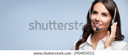 Portrait of support female phone operator in headset, looking up, with blank copyspace area for slogan or text message, on grey background. Consulting and assistance service call center. - stock photo