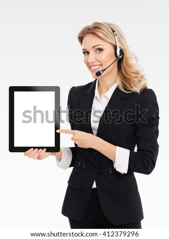 Portrait of support phone operator in headset showing blank no-name tablet pc monitor, with copyspace area for text or slogan, on grey background
