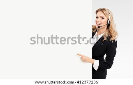 Portrait of support phone operator in headset showing blank signboard with copyspace area for text or slogan, on grey background