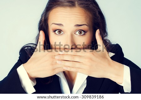Portrait of surprised excited brunette businesswoman covering with hands her mouth