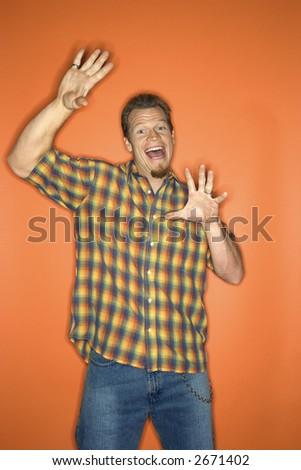 Portrait of surprised-looking adult Caucasian man on orange background. - stock photo