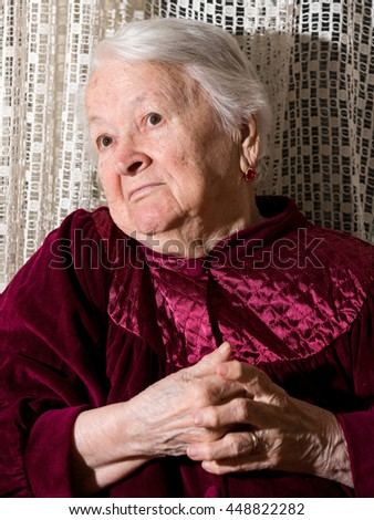 Portrait of surprised old woman at home - stock photo