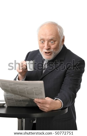 Portrait of surprised senior businessman drinking coffee reading newspaper, isolated on white.