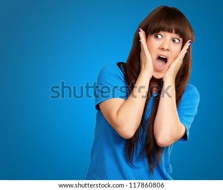 portrait of surprised woman isolated on blue background - stock photo