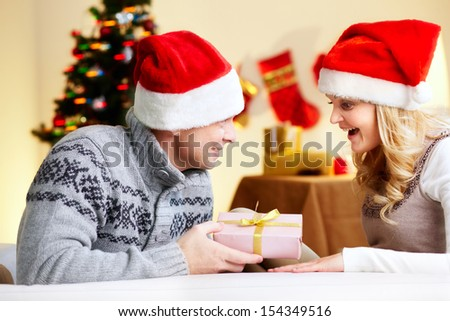 Portrait of surprised woman looking at giftbox in her husband hands on Christmas day - stock photo