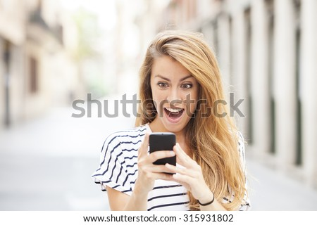 Portrait of surprised young girl looking at phone seeing news or photos with funny emotion on her face isolated outside city background. Human emotion, reaction, expression - stock photo