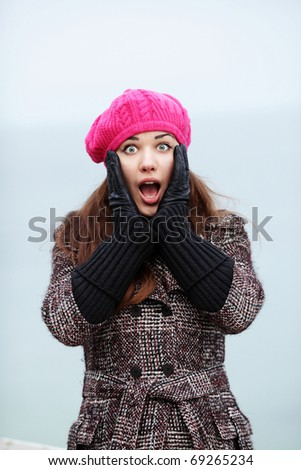 Portrait of surprised young lady looking to the camera outdoors - stock photo