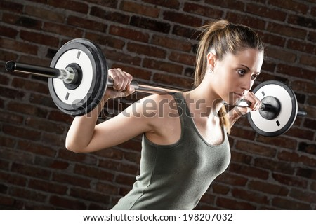 Portrait of Sweat beautiful girl lifting dumbbells on brick background  - stock photo