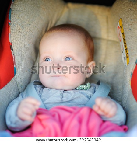 Portrait of sweet baby girl in car seat  - stock photo