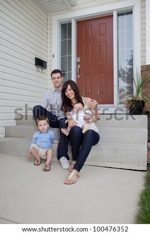 Portrait Of Sweet Family Sitting In Front Of Their House. - stock photo