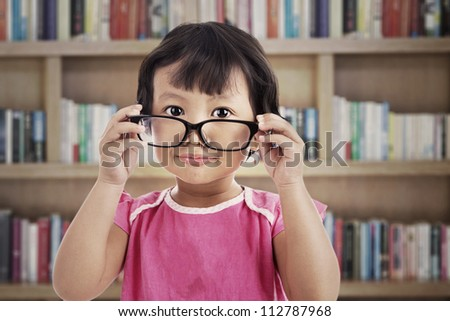 Portrait of sweet little girl in pink clothes wearing glasses. shot in the library
