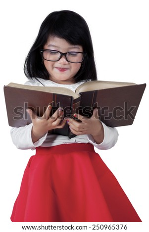 Portrait of sweet little girl wearing glasses while reading a textbook in the studio, isolated on white - stock photo
