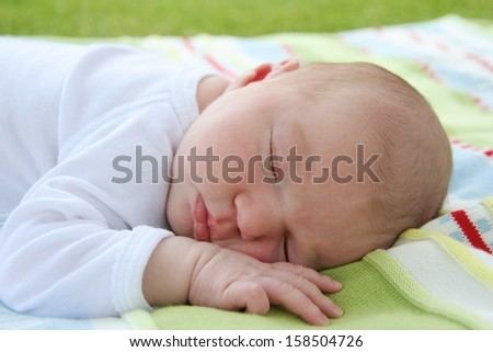 Portrait of sweet one week old baby sleeping peacefully outdoors on a colorful blanket