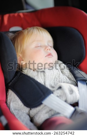 Portrait of sweet toddler boy sleeping in car seat - stock photo