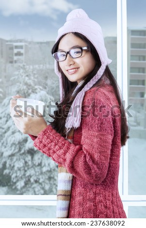 Portrait of sweet young girl wearing warm clothes and standing near the window while holding hot drink