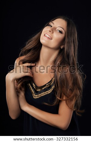 Portrait of tan pretty young woman with long brunette hair, smiling. Dark background. - stock photo