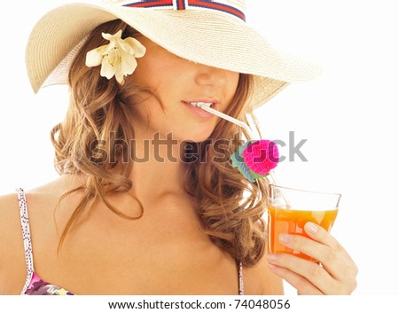 Portrait of tanned pretty young woman wearing hat and bikini clothes drinking fresh juice from glass with tubule. Isolated on white background with copyspace