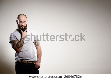 Portrait of tattooed bearded man - grey background - stock photo